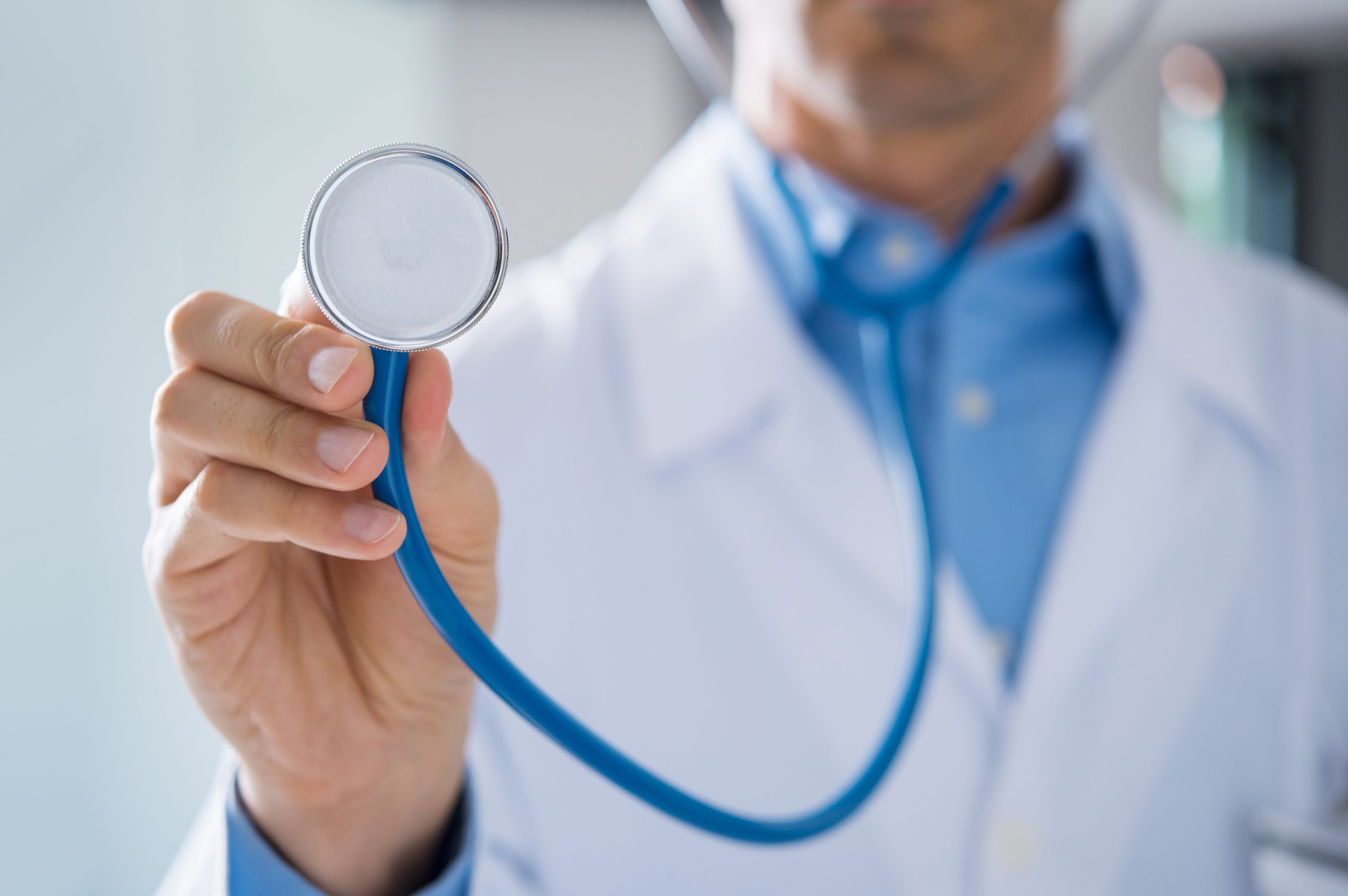 Male doctor showing stethoscope for checkup. Close up of doctor